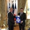 François Legault et Emmanuel Macron tiennent un drapeau du Québec encadré.