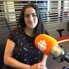 Une femme souriante aux cheveux longs noirs est assise dans un studio de Radio-Canada-Windsor. Devant elle il y a un micro de Radio-Canada