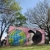 Des gens assis près d'une peinture où l'on voit le personnage de Mafalda regarder un globe-terrestre.