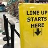 Une affiche jaune montre le début de la file d'attente aux caisses dans une épicerie.