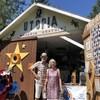Un couple se tient devant un cabanon transformé en magasin où les objets sont gratuits.