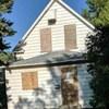 Une maison abandonnée avec les fenêtres et les portes condamnées à l'aide de planches de contreplaqué.