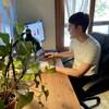 Un homme est assis devant son ordinateur, à la maison. Il y a une plante à l'avant-plan.
