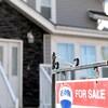 Une maison avec une pancarte à vendre.