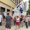 Une trentaine de personnes marche brandissant des drapeaux et des affiches.