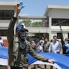 Un homme masqué lève le poing lors d'une manifestation au Nicaragua.