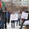 Des manifestants sont regroupés, deux d'entre eux tiennent des pancartes disant que le port du masque représente un contrôle.