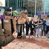Des jeunes tiennent des pancartes.
