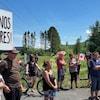 Un homme tient une pancarte «Ouvrez nos frontières!», il y a une dizaine de personnes à côté de lui et certains tiennent des drapeaux du Canada.