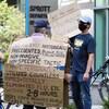 Un manifestant portant une affiche faisant la promotion d'une méthode pour supposément guérir la peste, la grippe et la fièvre jaune fait face à un contremanifestant lui montrant une affiche sur laquelle il a écrit « Protégez la science ».