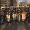 Des manifestants avec des pancartes.