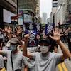 Des manifestants marchent dans la rue, les mains levées, certains avec des pancartes.