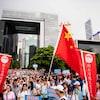 Une foule de manifestants brandissant des pancartes progouvernementales et des drapeaux de la Chine.