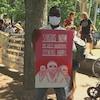 Un homme tient une affiche au milieu d'un rassemblement, sur laquelle on peut lire : « Un statut maintenant » en plusieurs langues.