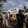 Un homme tient un pancarte où on peut lire « Vive l'armée ».