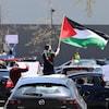 Un défilé de voitures. Des gens en sortent ou sont assis sur les toits des véhicules, brandissant des affiches et des drapeaux.
