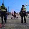 Un petit groupe de manifestants dont certains sont assis au centre d'une intersection fait face à deux policiers debout, de dos.