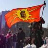 Des manifestants sont rassemblés devant un drapeau autochtone à Toronto.