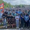 Des milliers d'étudiants masqués rassemblés avec pancartes et drapeaux.