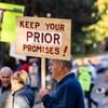 Des manifestants dans une rue de Vancouver, dont l'un porte une affiche qui indique : « Tenez vos promesses au sujet de Prior! »