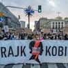 Des manifestants tiennent une banderole dans les rues de Varsovie.