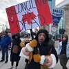 Une manifestante avec une pancarte où il est inscrit « la réconciliation est morte ».