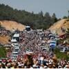 Une foule de gens manifestent sur une colline au milieu des arbres.