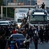 Des dizaines de personnes marchent sur la route, des voitures sont immobilisées. Certains manifestants ont grimpé sur le toit d'un camion.