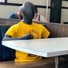 Un mannequin avec un chandail jaune assis à une table dans un restaurant.