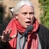 Manon Massé parle dans un micro à l'extérieur devant un édifice en briques.