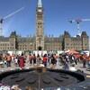 Des personnes réunies devant le parlement, à Ottawa.