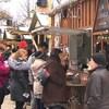 Plusieurs personnes sont présentes devant des kiosques extérieurs dans un marché de Noël à Longueuil.