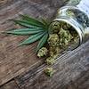 Pot de cannabis renversé sur une table en bois.