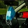 Des masques dans un véhicule, accrochés au miroir.