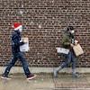 Deux personnes marchent sous la neige avec des sacs de magasinage à Toronto le 22 novembre 2020. L'un d'eux est coiffé d'une tuque de Noël.