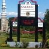 L'église de Sayabec avec une affiche aux couleurs de la municipalité en avant-plan.