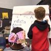Une fillette et un garçon écrivent sur un tableau des mots.