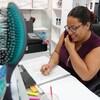La femme est au téléphone, et prend des notes sur papier avec autour d'elle brosses à cheveux.