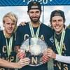 Trois joueurs de soccer tiennent le trophée de la Première ligue candienne de soccer
