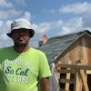 Un homme devant une cabane de fortune faite de bois avec une toiture en bardeaux d'asphalte.