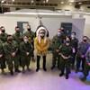 Le chef, en habits traditionnels, se tient au milieu du groupe de soldats. Tous portent un masque.