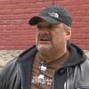 James Favel, portant une casquette, devant un mur de briques rouges.
