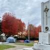 Plusieurs tentes en bordure d'un monument d'un parc vers la fin de l'automne.