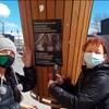 Deux femmes collant une affiche pour sensibiliser à l'environnement