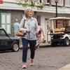 Une femme, avec un bout de papier dans la main, est dans une rue colorée et semble chercher un endroit.