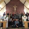 Une vingtaine de travailleurs saisonniers de l'industrie agricole dans une église avec trois célébrants.