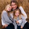 Photo avec une mère et deux petites filles blondes souriantes.