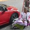 Une mendiante est assise à côté d'une voiture rutilante.