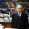 Un homme entouré de livres et autres documents.