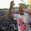 L'homme en t-shirt devant une foule de supporters.